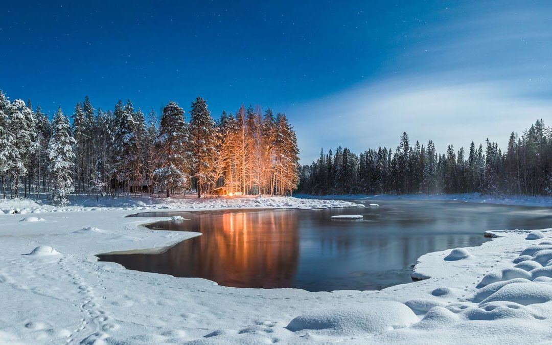 A lovely winter landscape scene: a semi-frozen lake with evergreen trees in the distance. Snow all around. Reused with permission of creator by East Coast Campers & More in Frankford, Delaware.