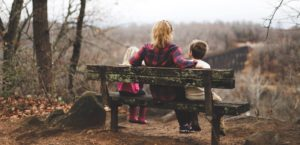 A woman sits between two children on a wooden bench in the forest. Photo by Benjamin Manley on Unsplash.